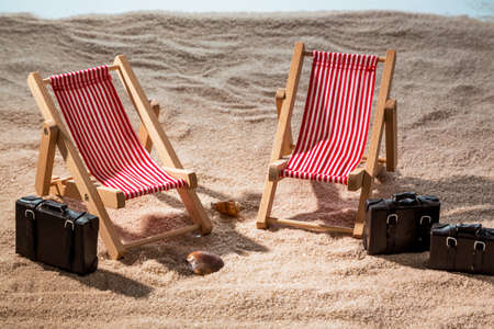 deck chairs: kkleine deck chairs on the sandy beach with suitcase Stock Photo