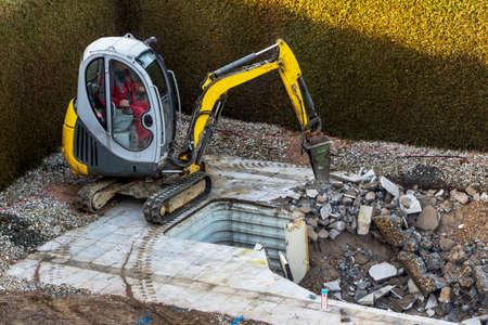 プライベートのスイミング プールの建設は掘削機によって解体します。 写真素材