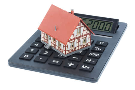 ongoing: residential building on a calculator, symbolic photo for home purchase, costs and savings