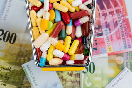 private insurance: tablets, shopping cart, swiss franc, symbol photo for drugs, health insurance, health care costs