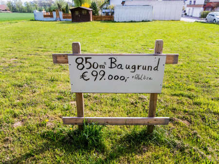 in a meadow there is a sign building for house for sale. building site for a new home. Stock Photo