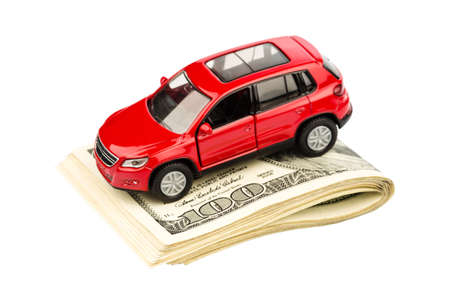 a car stands on dollar banknotes. cost of buying a car, fuel, insurance and other car costs Stock Photo