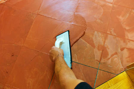 tile grout: a tiler carries on floor tiles on the grout. grouting of tiles. Stock Photo