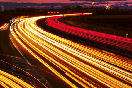 low light: many cars are driving at night on a highway and create light trails.