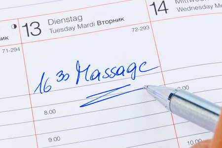 naturopaths: a date is entered on a calendar: massage Stock Photo