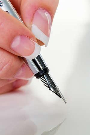 testament schreiben: eine Frau unterschreibt einen Vertrag oder ein Testament mit einem Füllfederhalter. Lizenzfreie Bilder