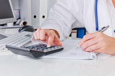 een arts in de chirurgie voert administratieve werkzaamheden. kosten in de spreekkamer. Stockfoto