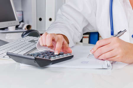 a doctor in the surgery performs administrative work. costs in the doctor's office.