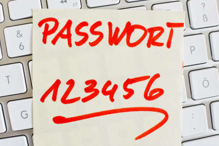 notieren: a sticky note is on the keyboard of a computer as a reminder: password 123456 Stock Photo