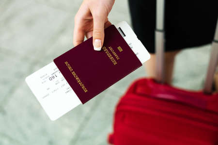 woman with passport and airline tickets at an airport waiting for her departure on holiday.