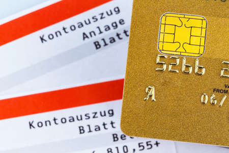 owe: a golden credit card and bank statement .. symbolic photo for cashless purchases and status symbols. Stock Photo