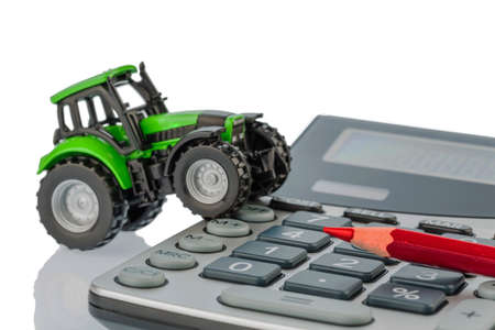 a tractor and a red pen is on a calculator. cost of gasoline, wear and insurance. costs and subsidies in agriculture photo