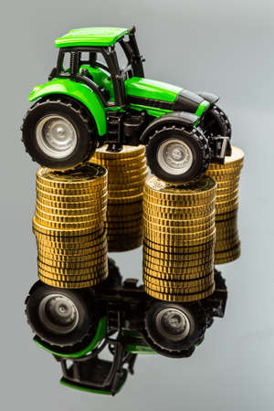reckon: farmers in agriculture have to reckon with rising costs. higher prices for feed, fertilizer and plants. tractor with coins