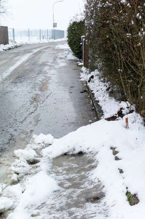 homeowners insurance: snow on sidewalk and street, symbol for accident risk and photo räumpflicht