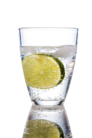 carbonated: a glass of fresh drinking water and a lime. mineral water as a thirst quencher. Stock Photo