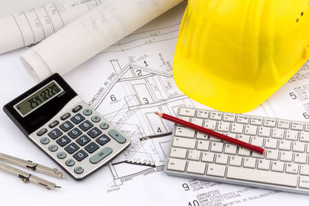 an architect's blueprint with the hard hat of a construction worker. symbolic photo for funding and planning of a new house. Standard-Bild