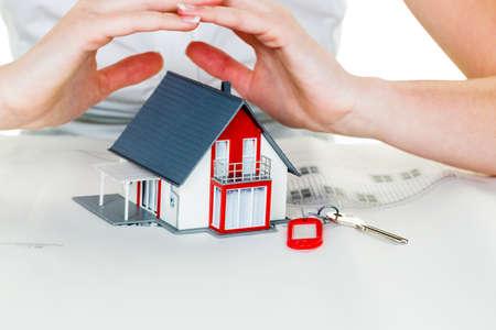 eine Frau schützt Ihr Haus und Heim. gute Versicherung und seriöse Finanzierung Ruhe. Lizenzfreie Bilder