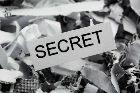 shredded paper tagged with secret, symbol photo for data destruction, banking secrecy and economic espionage