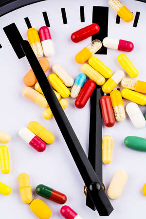 colorful capsules on a clock, symbol photo for healthcare, healthcare reform, reform backlog photo