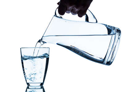 ewer: pure water is emptied into a glass of water from a pitcher. fresh drinking water