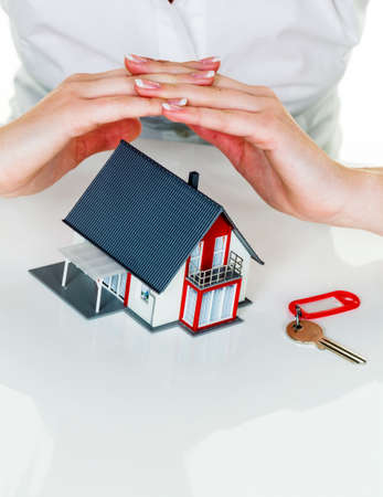 homeowners insurance: a woman protects your house and home. good insurance and reputable financing calm.
