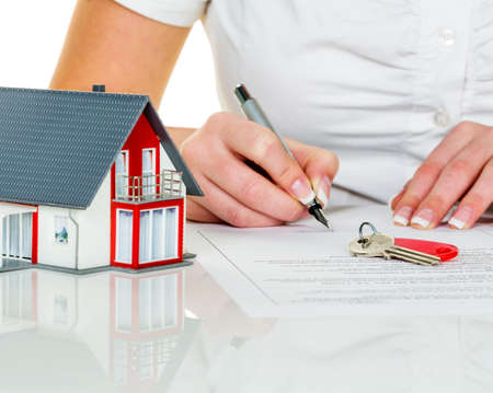 house sale: a woman signs a contract to purchase a home with a real estate agent.