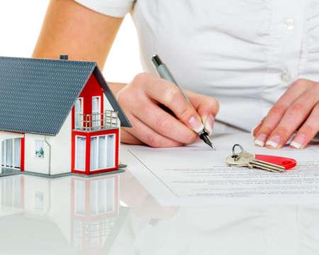 agente comercial: una mujer firma un contrato para comprar una casa con un agente de bienes raíces.