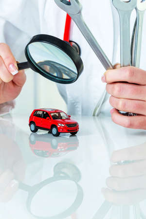 a model of a car is examined by a doctor. symbolic photo for workshop, service and car buying. photo