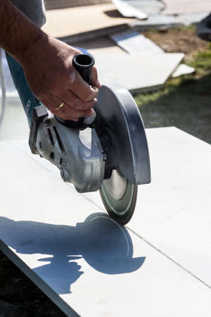 tile adhesive: a tiler at work. cuts boards with a cut-off wheel