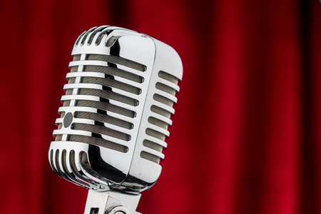 occurs: an old retro microphone against red velvet background. Stock Photo