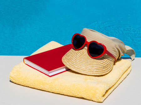 nice day: utensils for a nice and relaxing vacation day lying next to a swimming pool. relaxation on holiday. Stock Photo