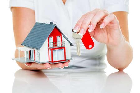 een makelaar voor onroerend goed met een huis en een sleutel. succesvolle verhuur en onroerend makelaars. Stockfoto