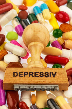 therapie: stamp on colorful tablets, symbol photo for depression, therapy and psychotropic drugs