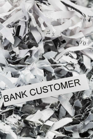 paper shredder: shredded paper tagged with bank customer, symbol photo for data destruction, customer data and banking secrecy