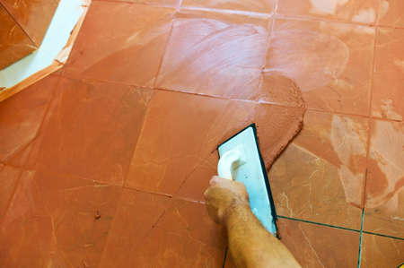 grout: a tiler carries on floor tiles on the grout. grouting of tiles. Stock Photo