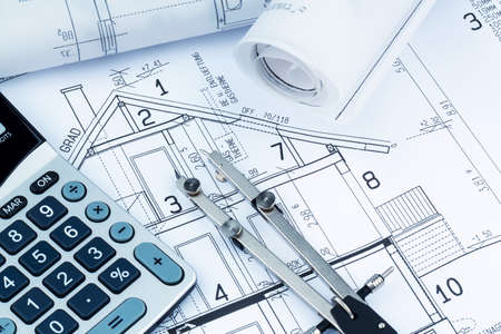 an architect's blueprint with a calculator. symbolic photo for funding and planning of a new house. Standard-Bild