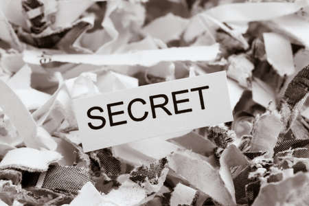 company secrets: shredded paper tagged with secret, symbol photo for data destruction, banking secrecy and economic espionage