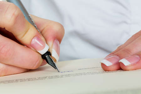 insurance services: a woman signs a contract or a will with a fountain pen.