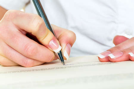 notieren: a woman signs a contract or a will with a pen.