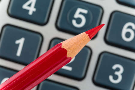 stocktaking: a red pen is on a calculator Stock Photo