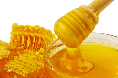 sweeten: a glass with honey against white background