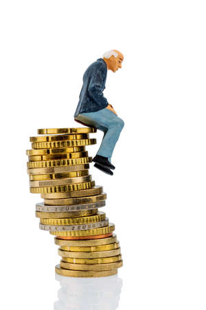 pensioner figure sitting on a pile of money photo
