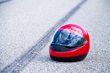 emergency braking: a motorcycle helmet on road Stock Photo