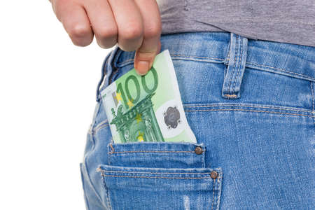 the hand of a young woman pulling a euro-bill from the pocket of her jeans photo