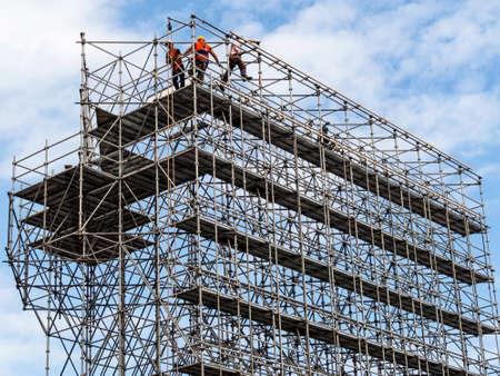operarios trabajando: los trabajadores de la construcción en un andamio  Foto de archivo