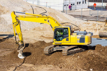 contruction: excavator on a construction site. excavator bucket with soil, ground work. Stock Photo