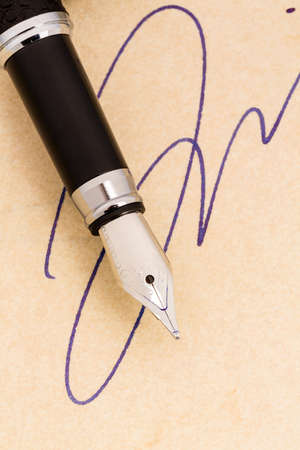 testament schreiben: eine Signatur und einem Füllfederhalter auf gelbem Papier. Symbolfoto für die Vertrags Testament und Graphologie Lizenzfreie Bilder