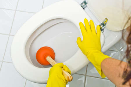 a clogged toilet is cleaned. with yellow latex gloves. Imagens