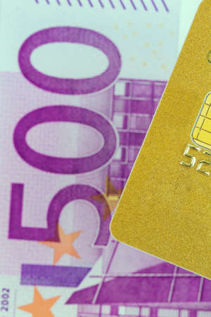 cashless: a golden credit card and euro banknotes. symbolic photo for cashless purchases and status symbols.