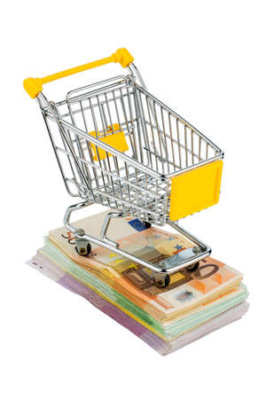 shopping cart is on banknotes, symbolic photo for shopping, purchasing power, money printing and inflation photo